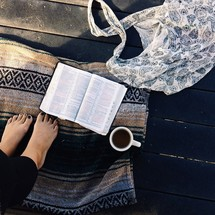 woman with bare feet standing on a blanket and a cup of coffee and an open BIble