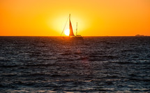 Silhouette of a sailboat in the ocean water at sunset.