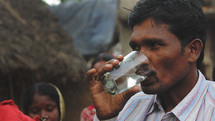 man drinking clean water in a rural Indian village
