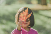 a young girl holding up a fall leaf