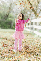 a young girl throwing fall leaves