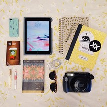 gift card, camera, novel, sunglasses, lipgloss, journal, iPad, iPhone, pen, and earbuds