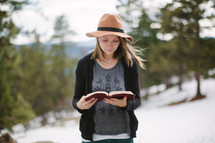 a young woman reading a Bible outdoors in snow