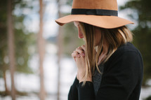 a woman in a hat praying outdoors