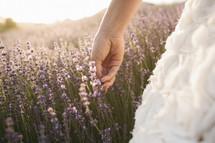 bride walking through a field touching purple wildflowers