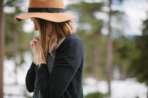 a woman in a hat with praying hands