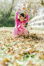 a young girl throwing through fall leaves