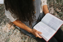 a woman sitting on a rock on a mountaintop reading a Bible