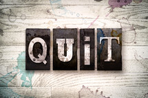 word quit on a white wash wood background