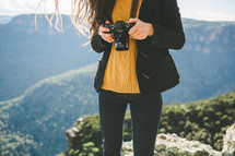 A woman holding a camera on a mountaintop.