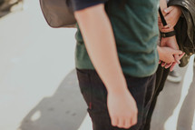 a couple with backpacks holding hands