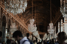 crowds of people under a hallway of chandeliers in Paris