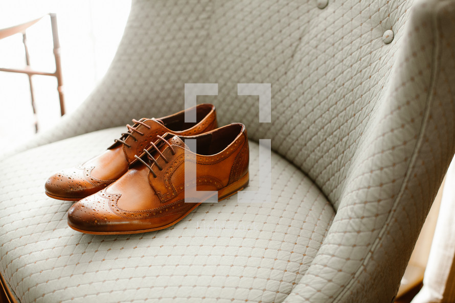 men's dress shoes on a chair