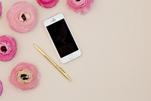 pink peonies, cellphone, and gold pen