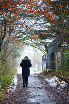 a woman walking on a muddy dirt road with melting snow