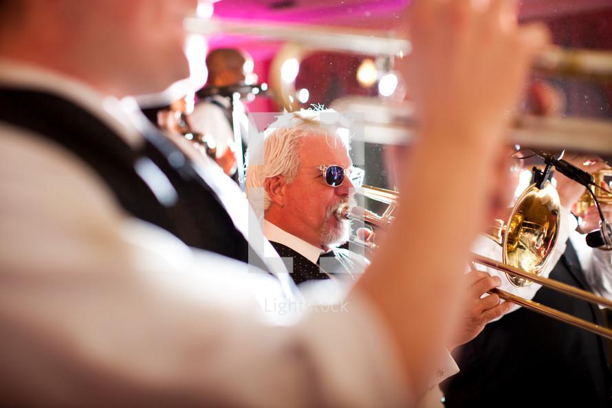 man wearing sunglasses playing a trombone