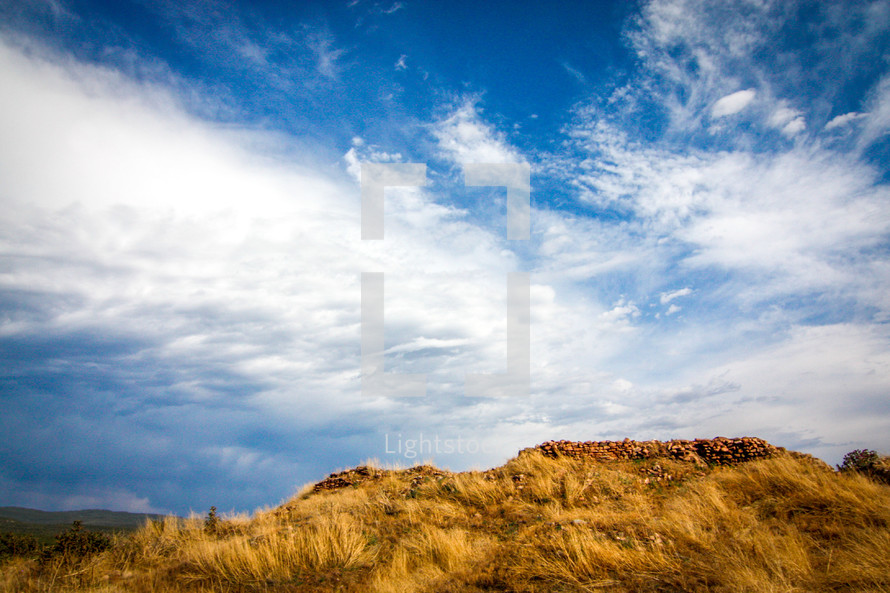 clouds over a hill with tall grass