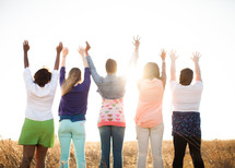 women with raised hands standing outdoors in a field