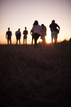 people outdoors in a field at sunset