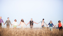 group walking together in a field holding hands