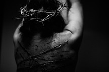 The suffering of Christ -- a beaten Jesus wearing His crown of thorns while bound to the cross by ropes.
