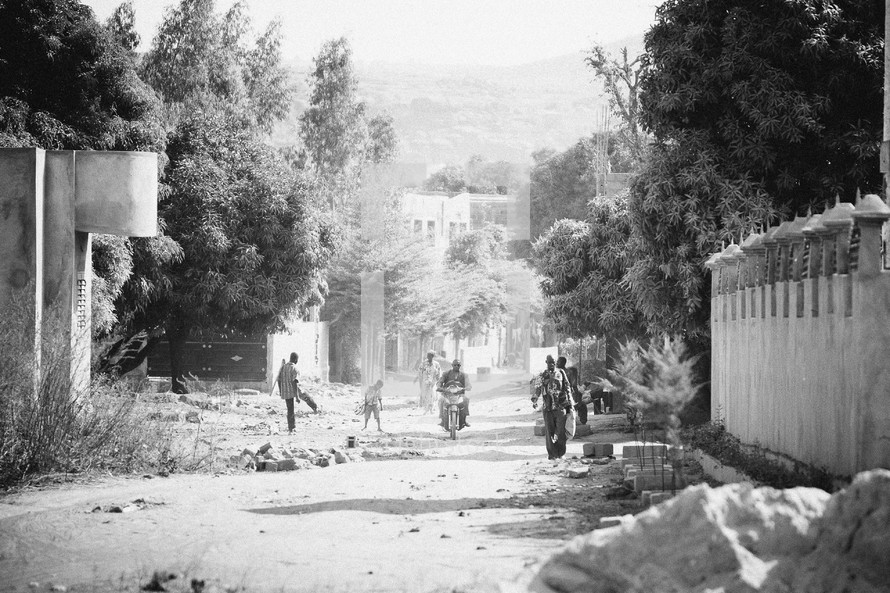 A group of men and boys walk down a dirt road.