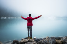 man standing on the shore of Lake Louise with hands raised