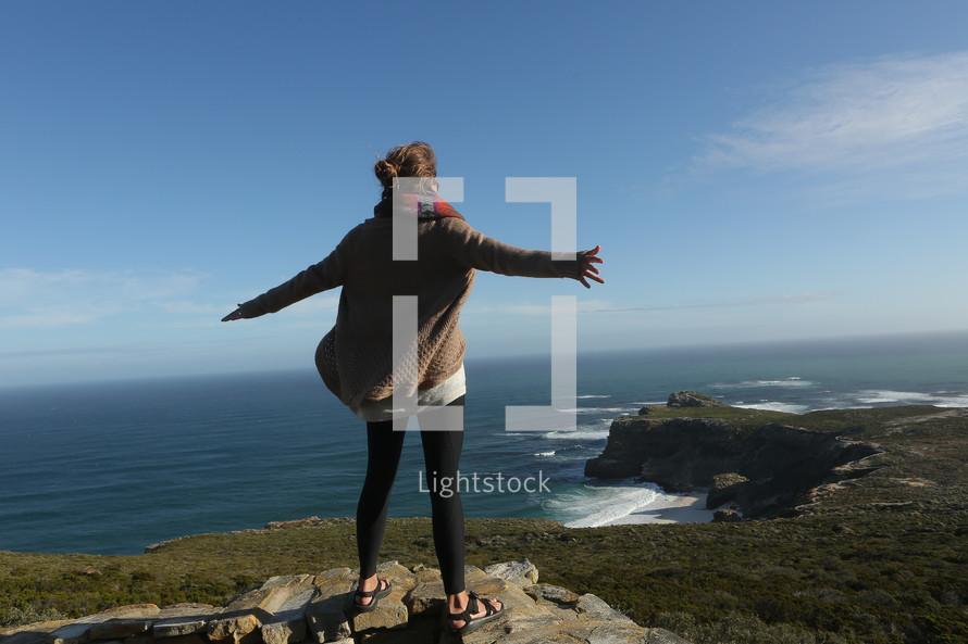 Woman standing on cliff overlooking ocean