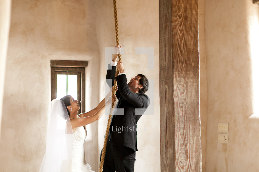 A bride and groom pull on a rope in order to ring the bell tower