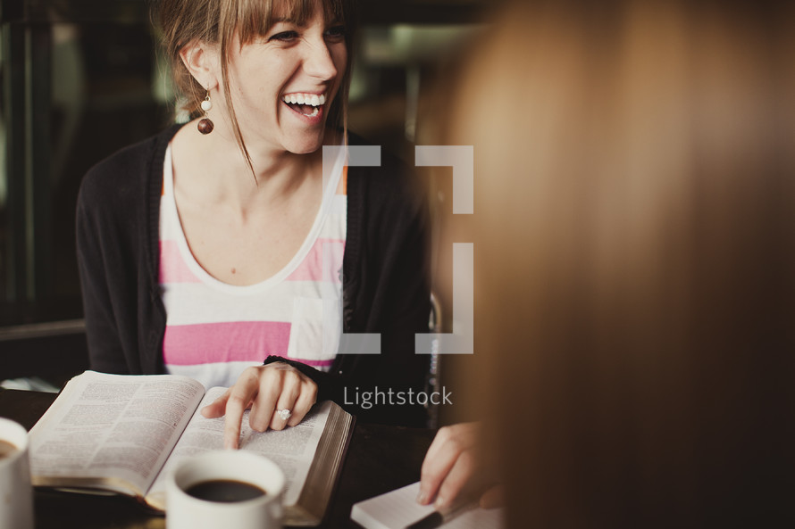 woman smiling pointing to the Bible during a Bible study