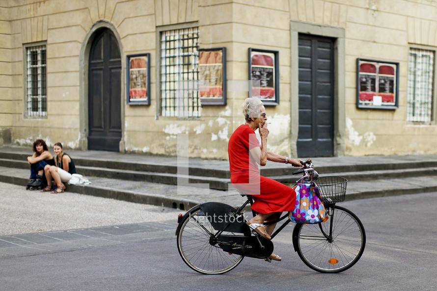 Elderly woman riding bicycle while smoking