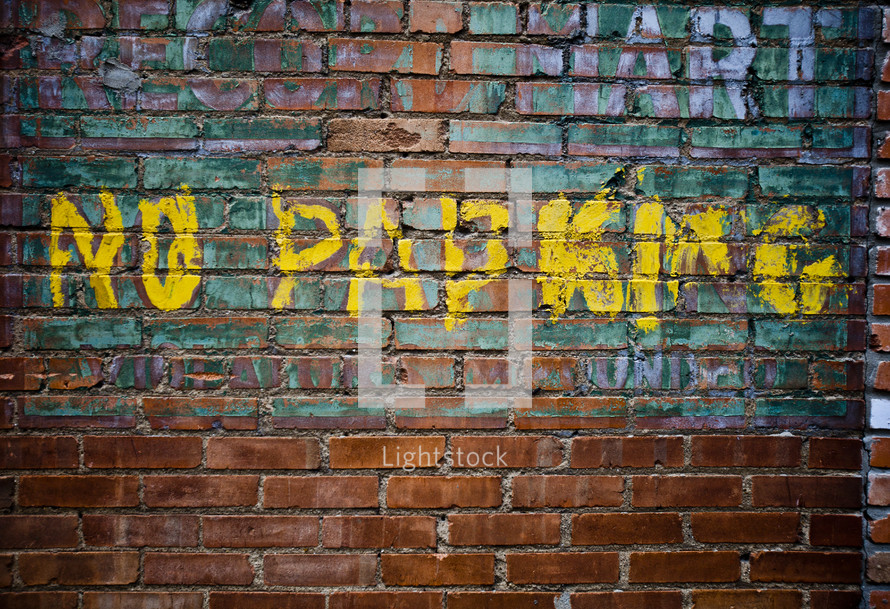 """No Parking"" painted on brick wall"