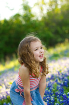 girl child in a field of Blue bonnets