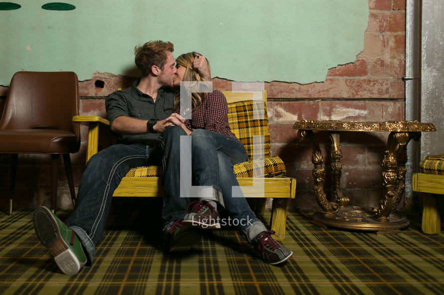 Couple kissing on a chair