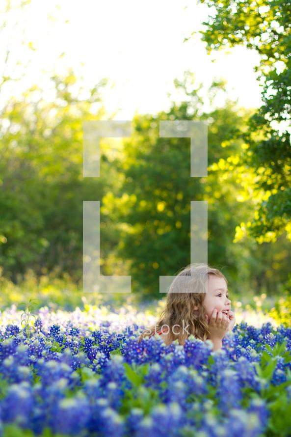 little girl lying in a field of blue bonnet flowers