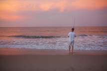 man standing on a beach with a fishing pole