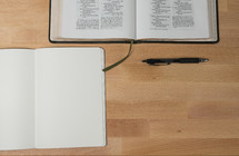 open Bible, open journal, and pen on a desk