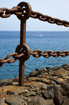 rusty metal chain in rock along a coastline