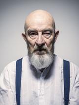 an elderly man in suspenders
