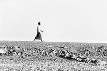 a man walking across the desert in a Ethiopia