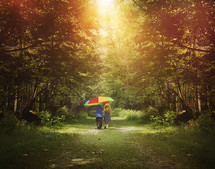 children walking on a path in a forest carrying a rainbow colored umbrella
