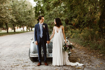 bride and groom standing in front of an old car