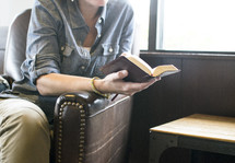 woman sitting in a leather chair reading a Bible