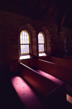 sunlight through windows in a church onto pews