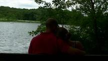 couple sitting on a bench near a lake