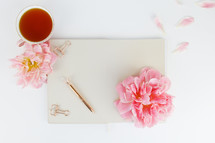 tea cup, notepad, pen, clips, and pink flowers on a desk