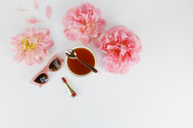 tea cup, pink spring flowers, red lipstick, sunglasses, and spoon against a white background