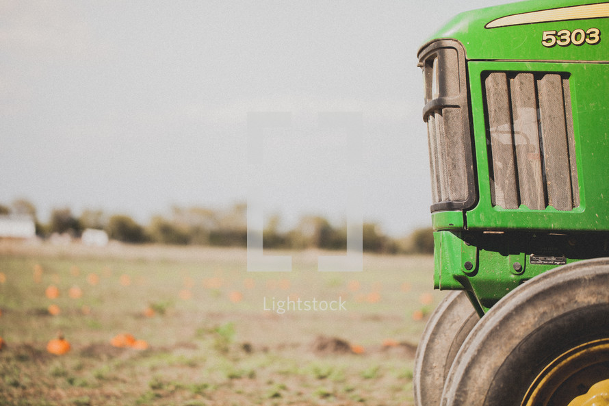 green tractor in a pumpkin patch