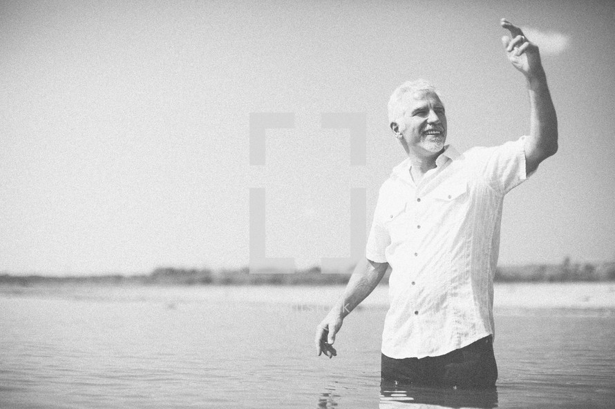 man standing in water calling others to be baptized