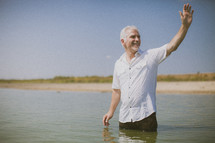 man standing in water waving